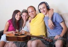 Cuatro personas jovenes con la guitarra y los auriculares Fotografía de archivo libre de regalías