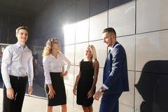 Cuatro personas jovenes hermosas, dos mujeres y dos hombres hablan, rechinan fotos de archivo