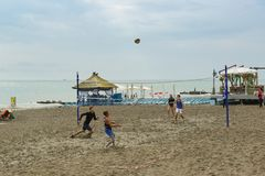 Cuatro personas jovenes juegan entusiasta a voleibol de playa en la costa del Mar Negro fotografía de archivo libre de regalías