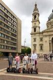 Cuatro personas jovenes que se colocan en un segway delante de la basílica de Budapest Imagen de archivo libre de regalías