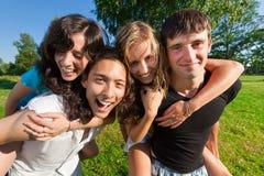Cuatro personas jovenes que se divierten en el parque Imagen de archivo libre de regalías