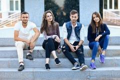 Cuatro personas jovenes que se sientan en las escaleras al aire libre con los teléfonos móviles Imagen de archivo libre de regalías