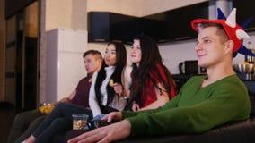 Cuatro personas jovenes que ven la TV y que mueven de un tirón las cadenas de televisión almacen de metraje de vídeo