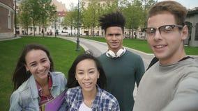 Cuatro personas multiétnicas que toman el selfie, hablando, sonriendo, teniendo buen día metrajes