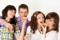 Cuatro personas que comen la pizza Imágenes de archivo libres de regalías