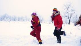 Cuatro personas que corren junto en paisaje del invierno almacen de video