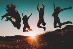 Cuatro personas que saltan sobre el cielo en la puesta del sol Fotos de archivo