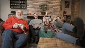 Cuatro personas que se relajan en casa y que juegan al videojuego almacen de video
