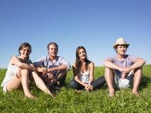 Cuatro personas que se sientan en la hierba Imagenes de archivo