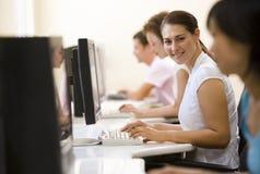 Cuatro personas que se sientan en sala de ordenadores Imagen de archivo