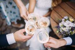 Cuatro personas que tuestan el champán en un día de boda fotografía de archivo