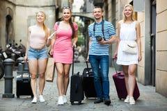 Cuatro personas que viajan amistosas que caminan en ciudad Fotografía de archivo libre de regalías