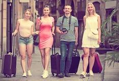 Cuatro personas que viajan jovenes que caminan en ciudad Fotos de archivo libres de regalías