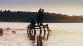 Cuatro pescados de la pesca del pescador de los muchachos en el embarcadero de madera en el lago en el bosque de la puesta del so almacen de metraje de vídeo