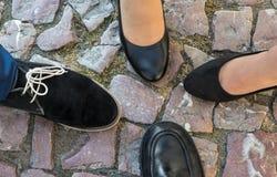 Cuatro pies en zapatos formales en los guijarros históricos Visión superior fotos de archivo