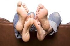 Cuatro pies encima mueven hacia atrás del sofá Fotografía de archivo