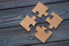 Cuatro piezas del rompecabezas se combinan en un solo entero en un fondo de madera azul fotografía de archivo