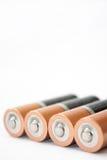 Cuatro pilas alcalinas AA en un fondo blanco Foto de archivo libre de regalías