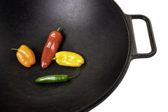 Cuatro pimientas coloridas en un Wok Fotos de archivo libres de regalías