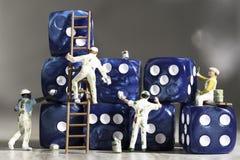 Cuatro pintores miniatura de la gente que pintan dados azules con las pipas blancas imágenes de archivo libres de regalías