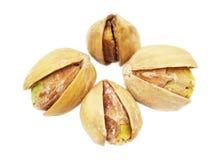 Cuatro pistachos en el primer blanco del fondo Imagen de archivo