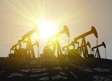 Cuatro pozos de petróleo silueteados contra puesta del sol Foto de archivo libre de regalías
