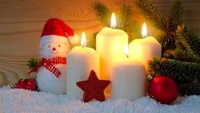Cuatro quemas blancas y muñeco de nieve de las velas del advenimiento Fotos de archivo libres de regalías