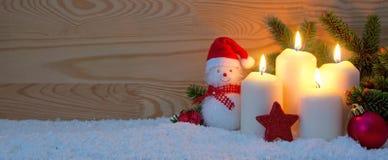 Cuatro quemas blancas y muñeco de nieve de las velas del advenimiento Imagenes de archivo