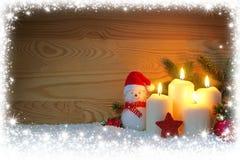 Cuatro quemas blancas y muñeco de nieve de las velas del advenimiento Imagen de archivo