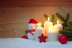 Cuatro quemas blancas y muñeco de nieve de las velas del advenimiento Foto de archivo