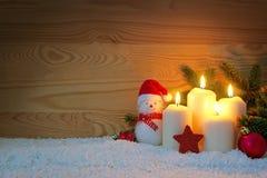 Cuatro quemas blancas y muñeco de nieve de las velas del advenimiento Fotos de archivo