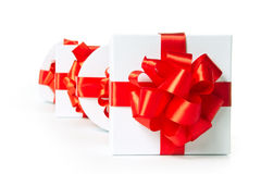 Cuatro rectángulos de regalo blancos con la cinta roja del satén Foto de archivo