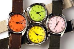 Cuatro relojes coloridos Imágenes de archivo libres de regalías