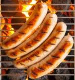 Cuatro salchichas llamaron Bratwurst, asando a la parrilla sobre los carbones calientes en un Bbq Fotografía de archivo