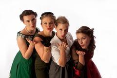 Cuatro señoras jovenes preciosas que soplan una serie del beso Foto de archivo