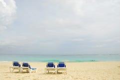 Cuatro sillas de playa del sol Fotos de archivo libres de regalías