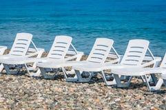 Cuatro sillas de playa plásticas blancas en la playa Fotografía de archivo