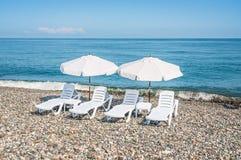 Cuatro sillas de playa plásticas blancas y dos parasoles blancos en el  Fotos de archivo
