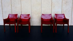 Cuatro sillas rojas en el piso negro cerca de la pared blanca imagen de archivo libre de regalías