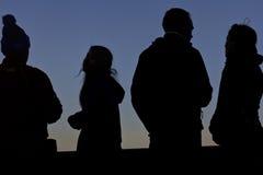 Cuatro siluetas en la puesta del sol Imágenes de archivo libres de regalías