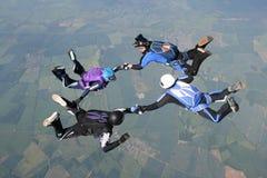 Cuatro skydivers que llevan a cabo las manos Imagenes de archivo