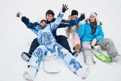 Cuatro snowborders se sientan en nieve Foto de archivo