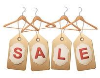Cuatro suspensiones de madera con los precios que forman la venta de la palabra Fotografía de archivo