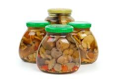 Cuatro tarros de cristal con las setas adobadas fotos de archivo libres de regalías