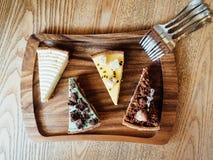Cuatro tartas en una bandeja de madera de la porción Imágenes de archivo libres de regalías