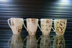 Cuatro tazas blancas con diversos modelos en un fondo hermoso imagen de archivo