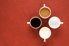 Cuatro tazas con leche y café fotos de archivo