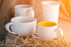 Cuatro tazas de café en el mantel beige Imagen de archivo libre de regalías