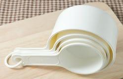 Cuatro tazas de medición plásticas blancas en el tablero de madera Fotos de archivo