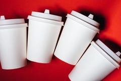Cuatro tazas de papel en fondo rojo fotos de archivo libres de regalías